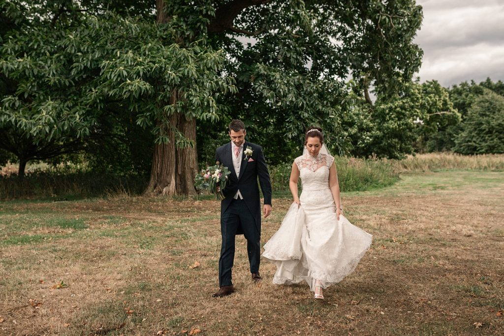 Bride and groom walking at Offley Place Wedding, taken by Becky Harley Photography