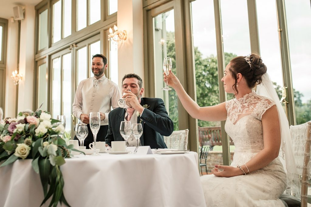 bride and groom drinking a toast at Offley Place Wedding, taken by Becky Harley Photography