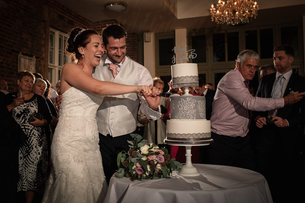 Bride and Groom cutting the wedding cake at Offley Place Wedding, taken by Becky Harley Photography