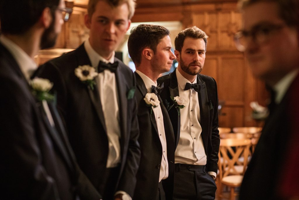 Groom and ushers greeting guests at Oxford Town Hall wedding taken by Becky Harley Photography