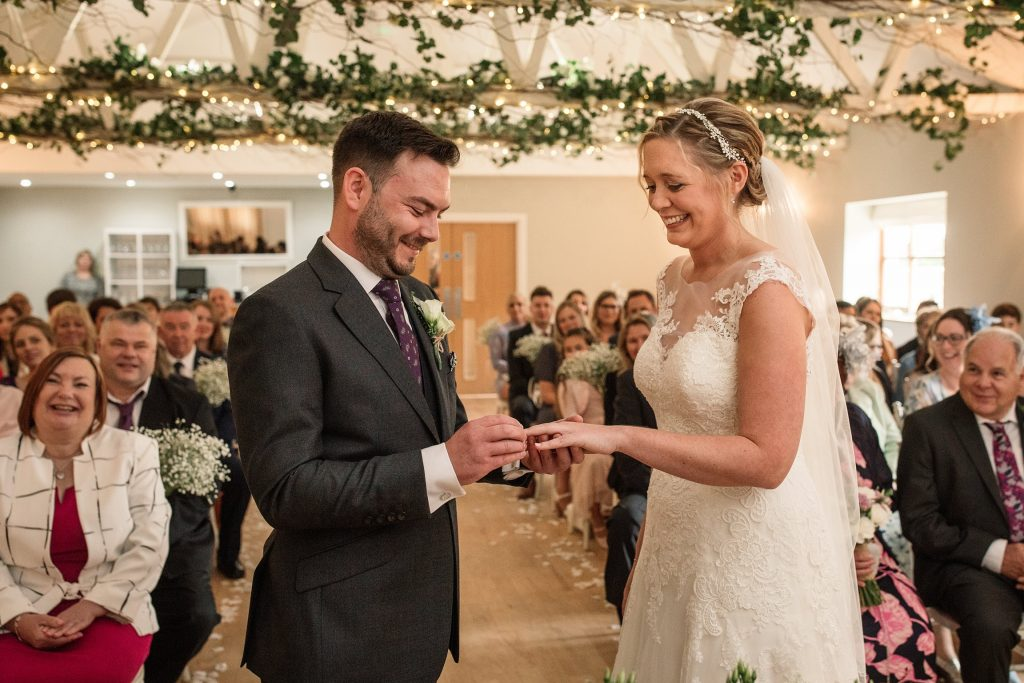 Bride and Groom exchanging rings at relaxed, rustic Milling Barn Wedding, taken by Becky Harley Photography