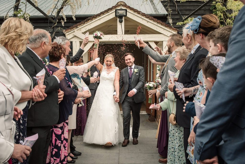 Bride and groom with confetti at relaxed, rustic Milling Barn Wedding, taken by Becky Harley Photography