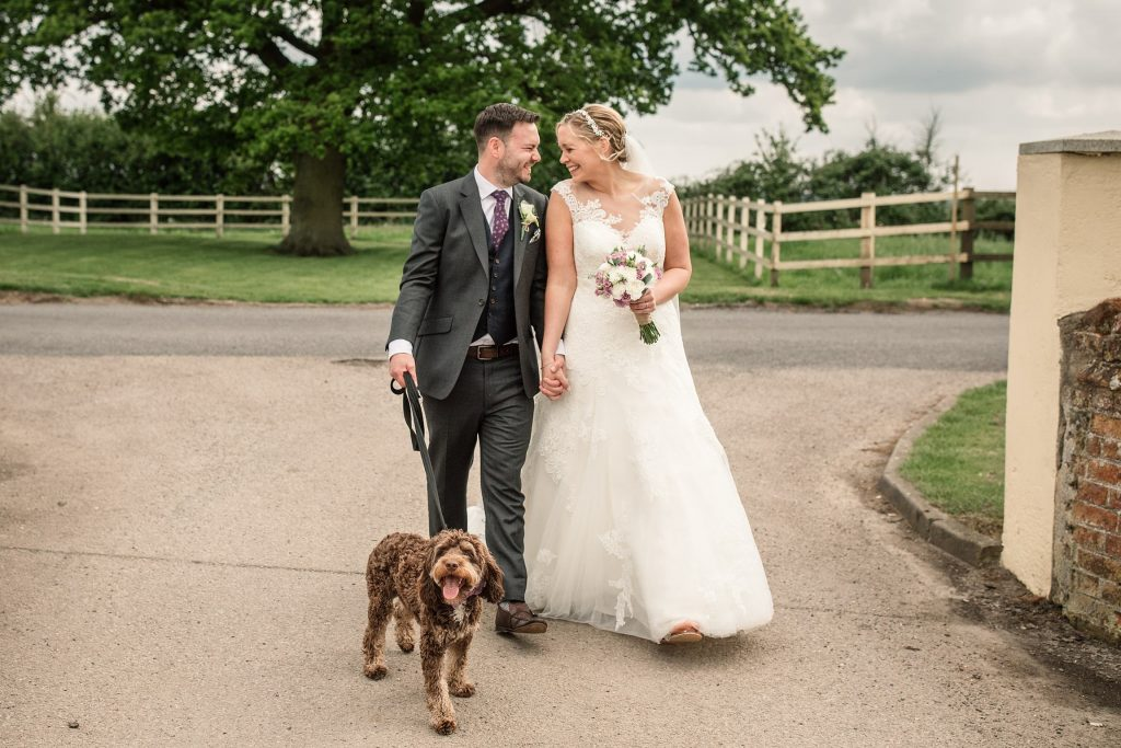 Bride and groom walking dog at relaxed, rustic Milling Barn Wedding, taken by Becky Harley Photography