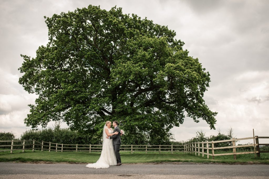 Bride and Groom with oak tree at relaxed, rustic Milling Barn Wedding, taken by Becky Harley Photography