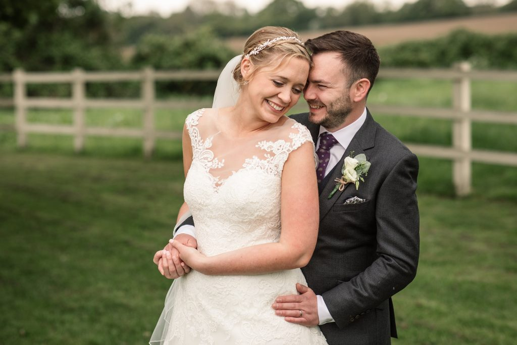 Bride and groom cuddling at relaxed, rustic Milling Barn Wedding, taken by Becky Harley Photography