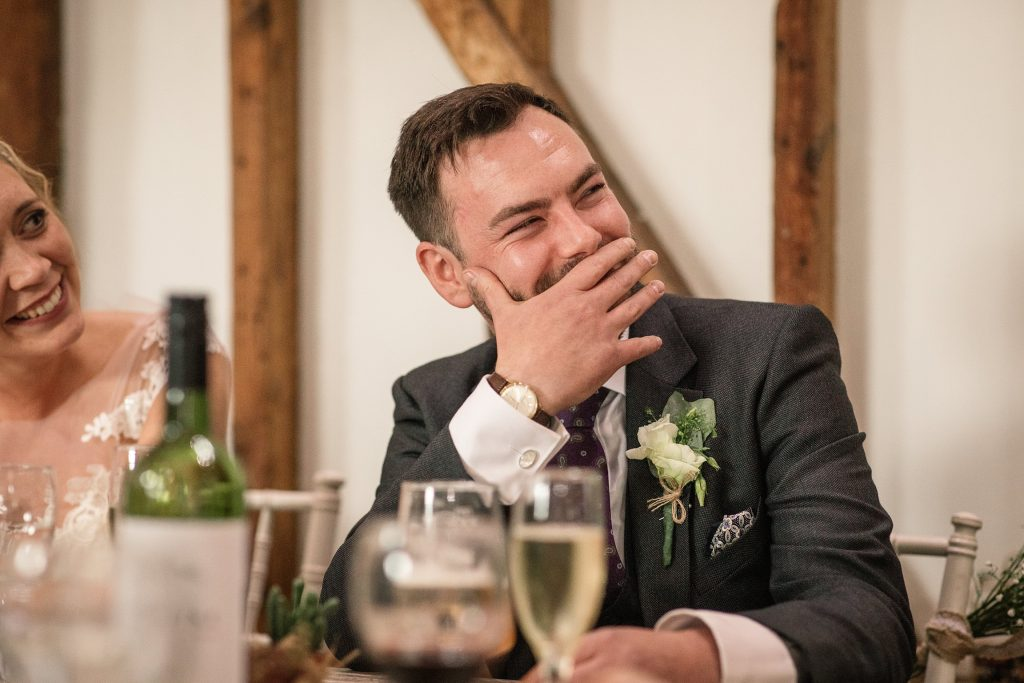 Groom laughing at speeches at relaxed, rustic Milling Barn Wedding, taken by Becky Harley Photography