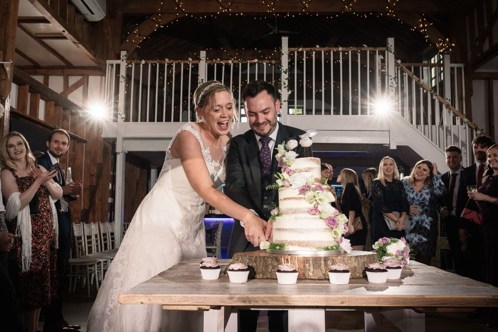 Bride and groom cutting cake at relaxed, rustic Milling Barn Wedding, taken by Becky Harley Photography