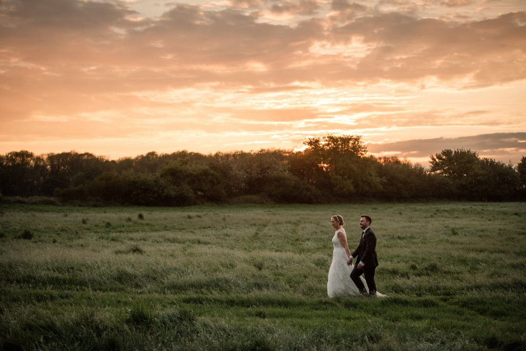 Bride and Groom walking in field with sunset at relaxed, rustic Milling Barn Wedding, taken by Becky Harley Photography