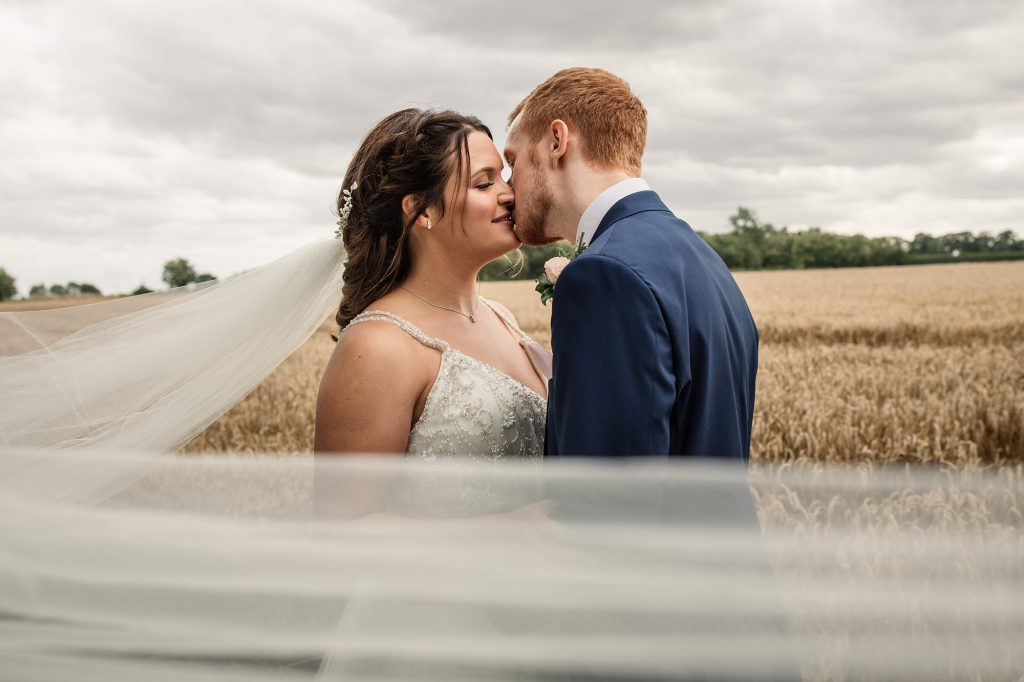Bride and Groom kissing with veil blowing in wind at Granary Estates Wedding taken by Becky Harley Photography