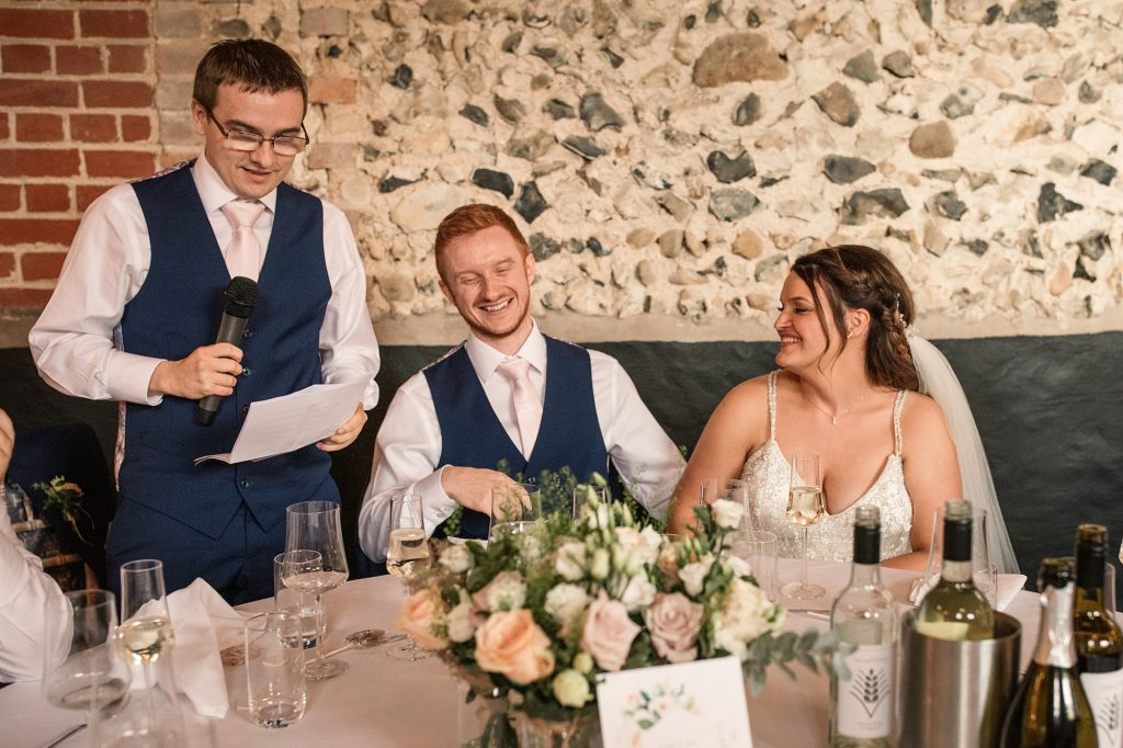 Best man speaking while Bride and Groom laugh at Granary Estates Wedding taken by Becky Harley Photography