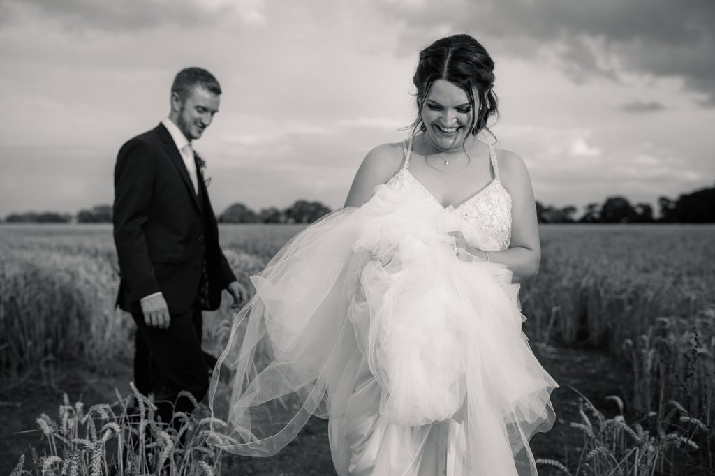 Bride and groom walking out of cornfield at Granary Estates Wedding taken by Becky Harley Photography