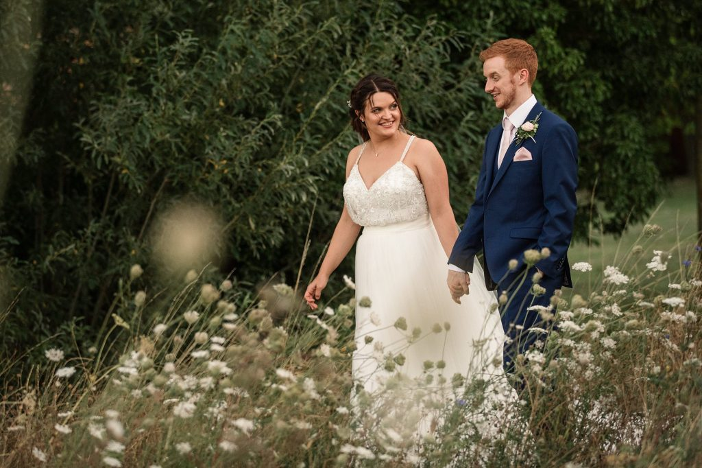 Bride and Groom walking by wildflowers at Granary Estates Wedding taken by Becky Harley Photography