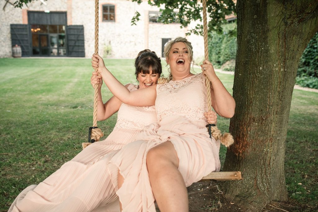 Bridesmaids laughing on swing at Granary Estates Wedding taken by Becky Harley Photography