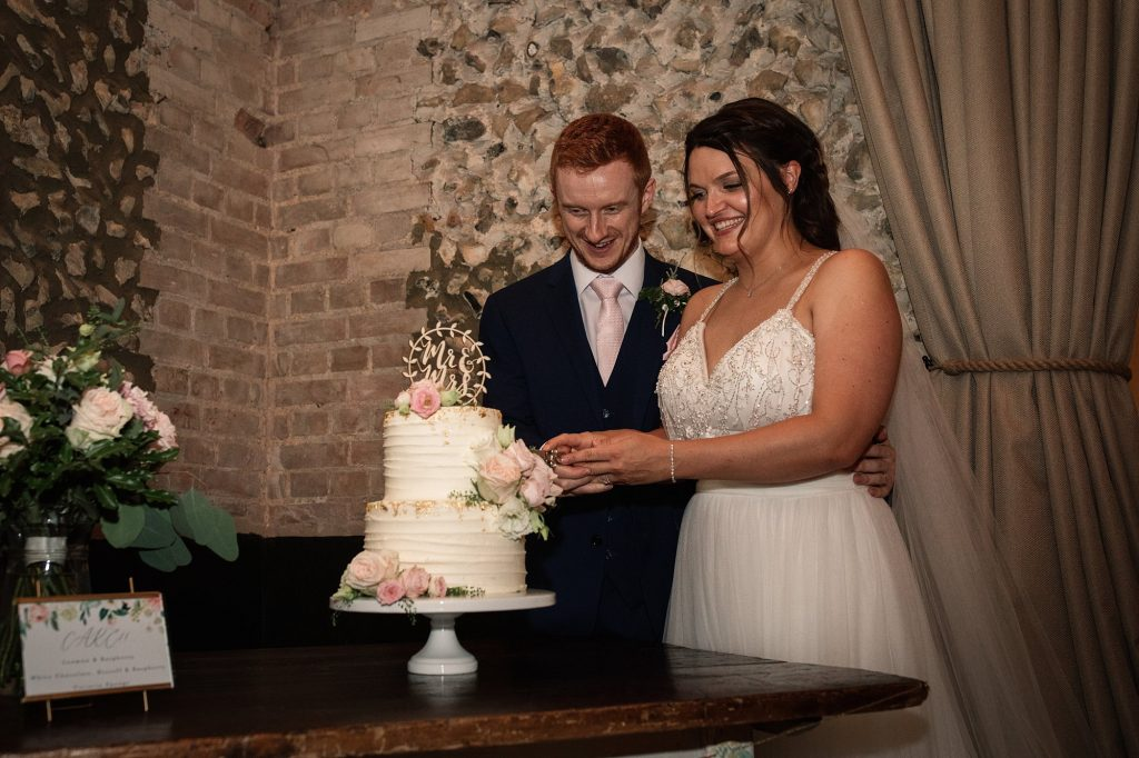 Bride and groom cutting cake at Granary Estates Wedding taken by Becky Harley Photography