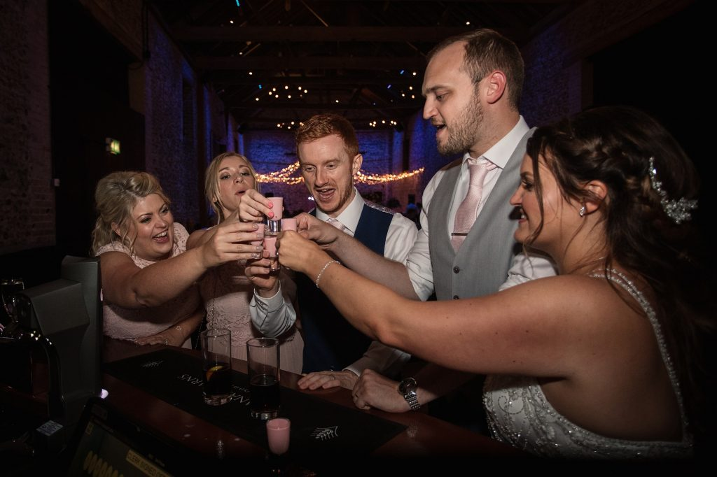 Bride and groom doing shots with bridesmaids and usher at Granary Estates Wedding taken by Becky Harley Photography