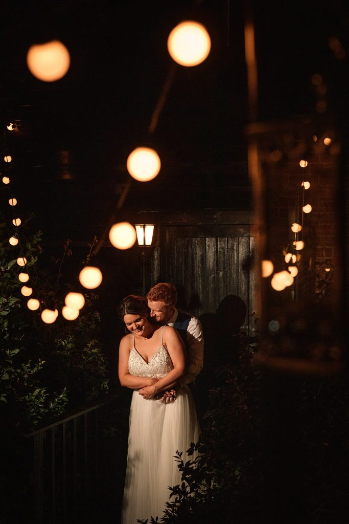 Bride and groom with festoon lighting at Granary Estates Wedding taken by Becky Harley Photography