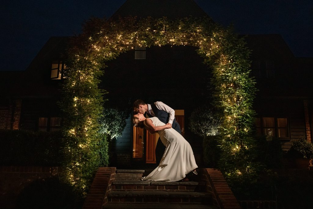 Bride and Groom under lit archway , one of the best barn wedding venues in Hertfordshire. Taken by Becky Harley Photography