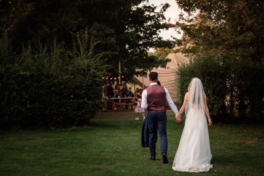 Bride and Groom walking to wedding reception at Henry Moore Foundation, one of the best barn wedding venues in Hertfordshire, taken by Becky Harley Photography