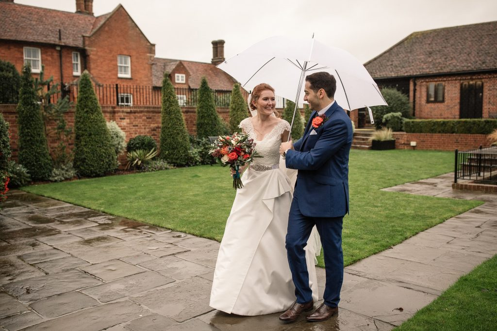Bride and groom walking in the courtyard at Coltsfoot Country Retreat, one of the best barn wedding venues in Hertfordshire. Taken by Becky Harley Photography