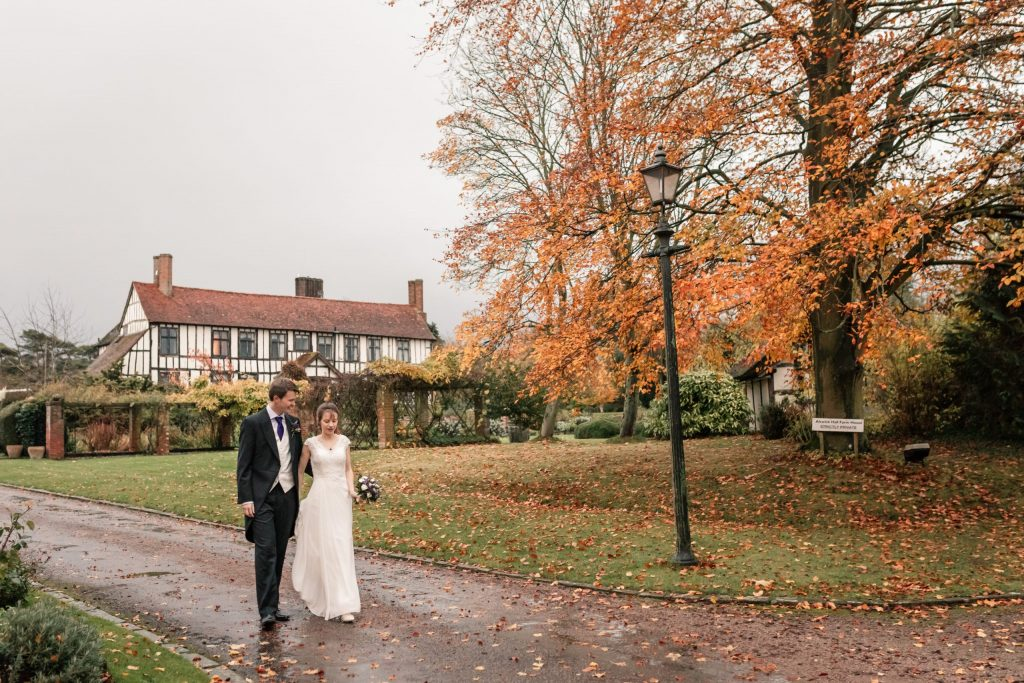 Couple walking in the autumnal grounds at Alswick Barn, one of the best barn wedding venues in Hertfordshire. Taken by Becky Harley Photography
