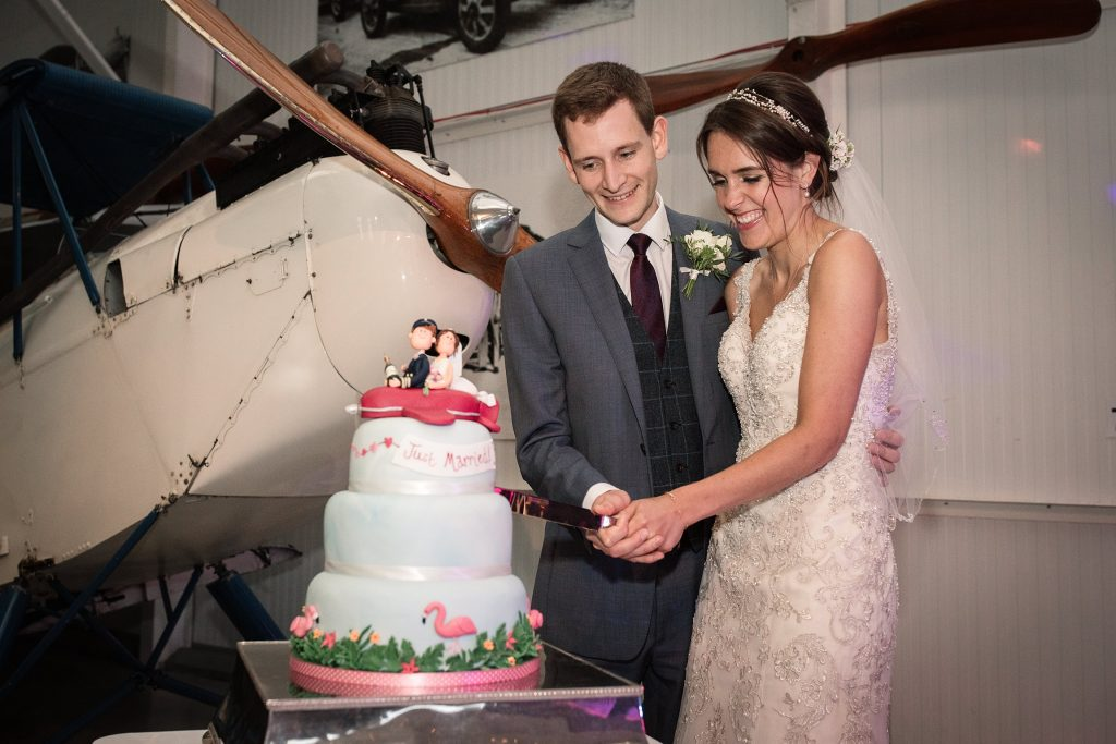 bride and groom cutting cake at Shuttleworth Collection Wedding, taken by Becky Harley Photography