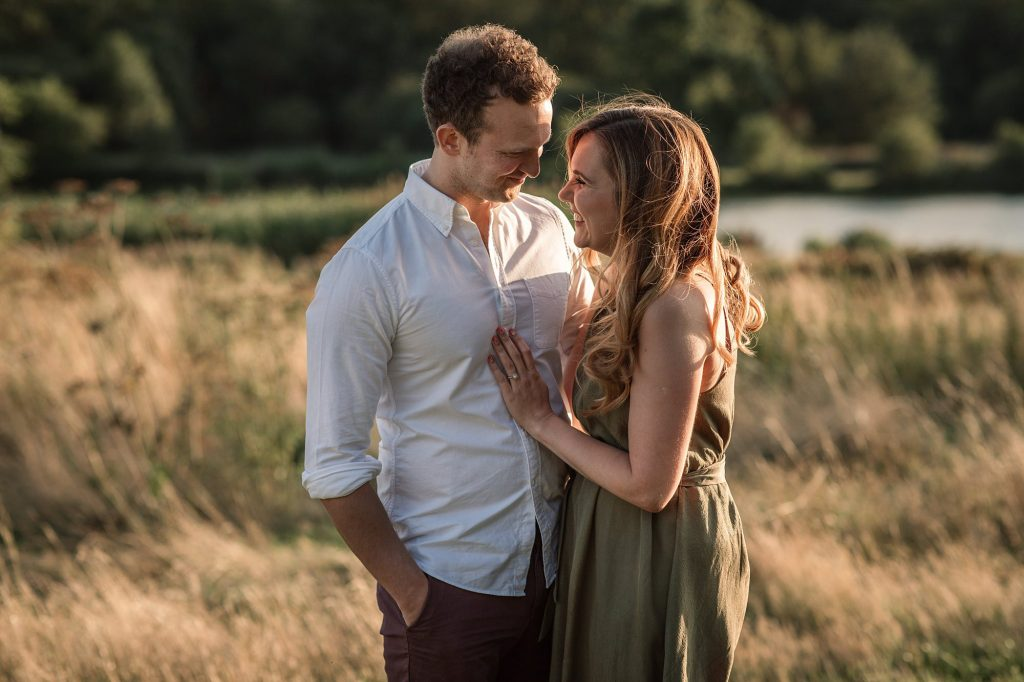 Couple cuddling at sunset engagement shoot taken by Becky Harley Photography
