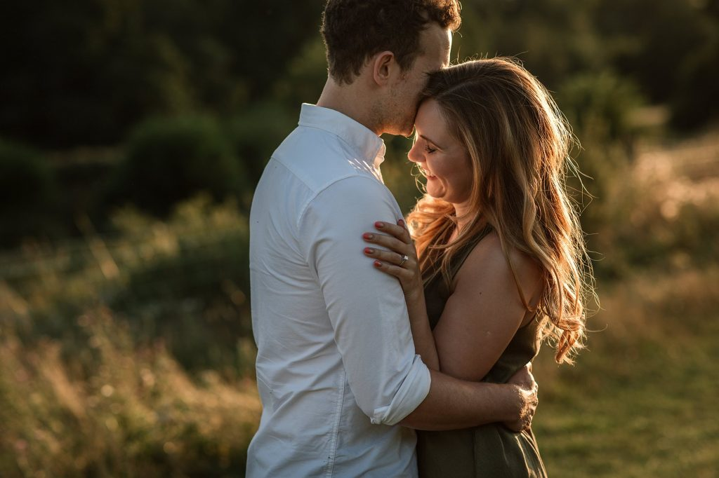 Couple embracing at sunset engagement shoot taken by Becky Harley Photography