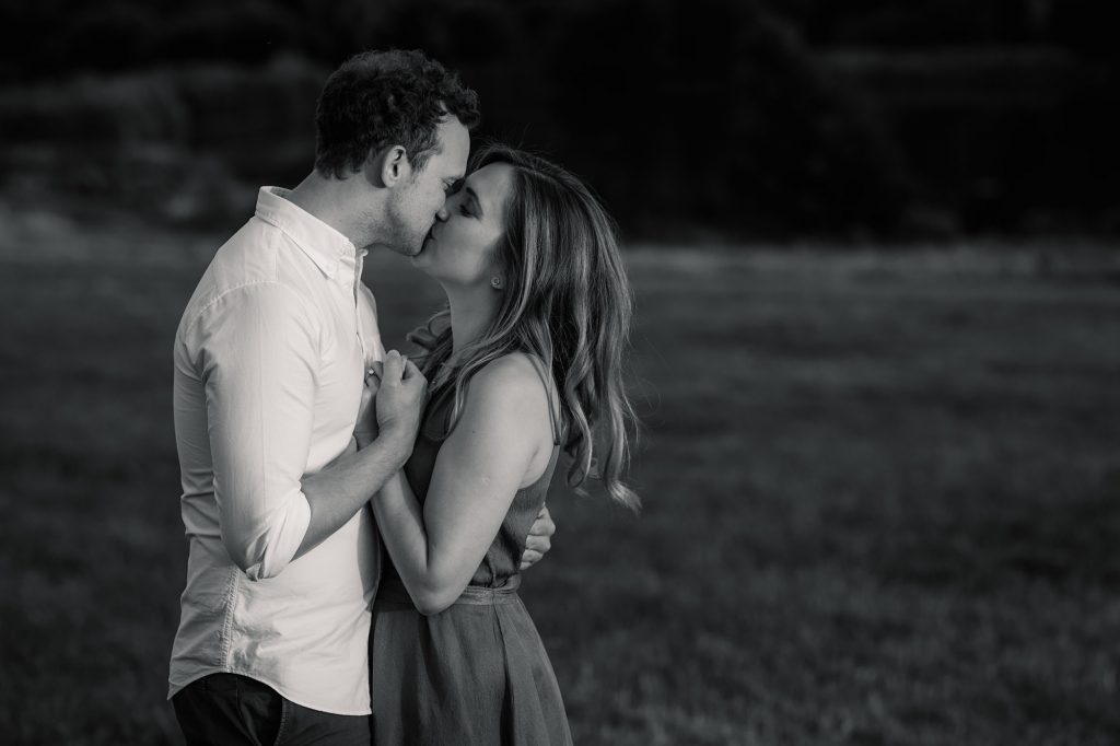 Couple kissing at sunset engagement shoot taken by Becky Harley Photography