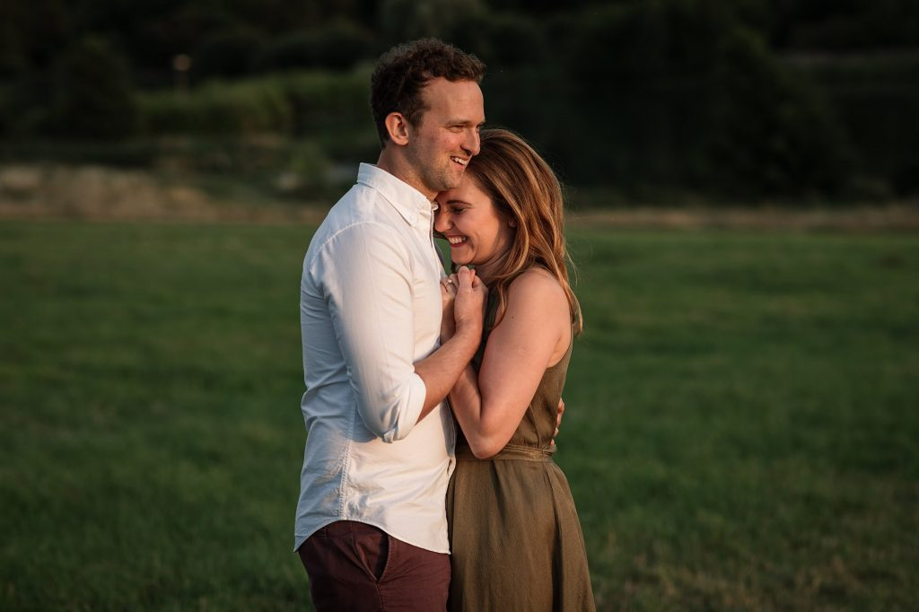 Couple embracing and smiling at sunset engagement shoot taken by Becky Harley Photography