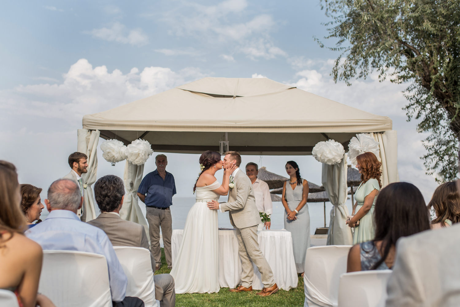 Bride and Groom kiss during Greek wedding ceremony. Destination wedding planning, taken by Becky Harley Photography