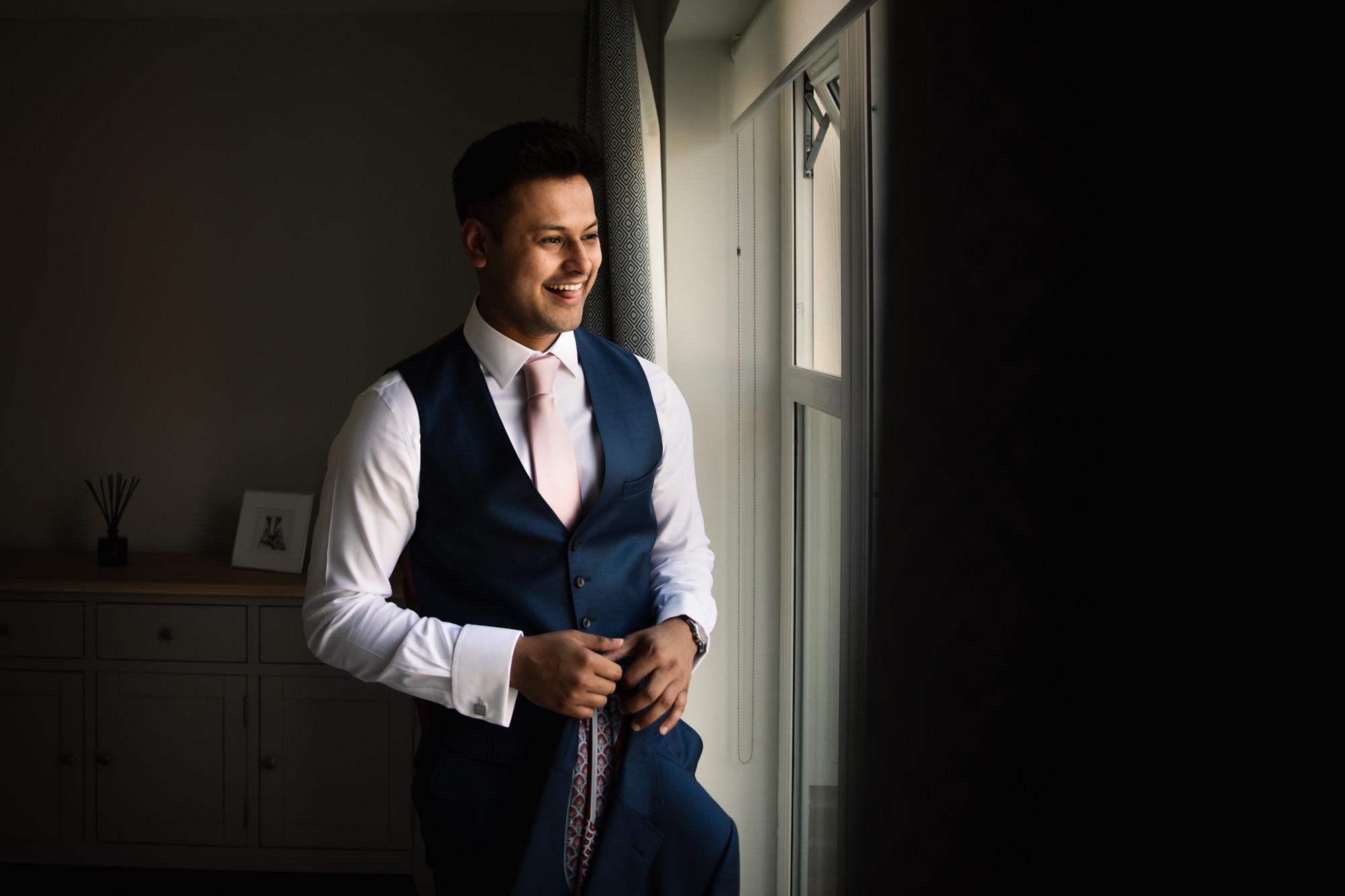 Groom stood by window getting ready for wedding