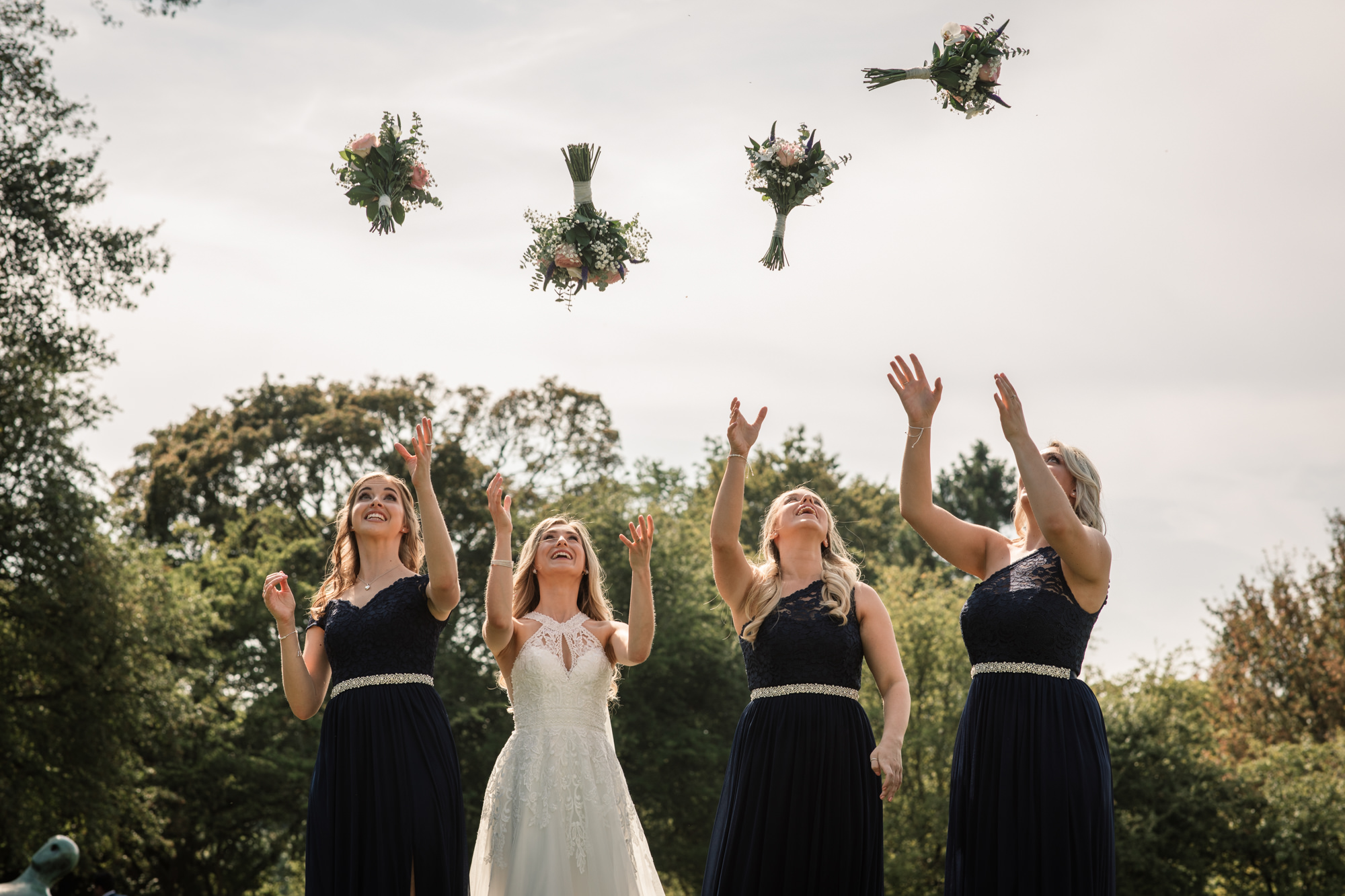 Bride and bridesmaids throwing their wedding bouquets
