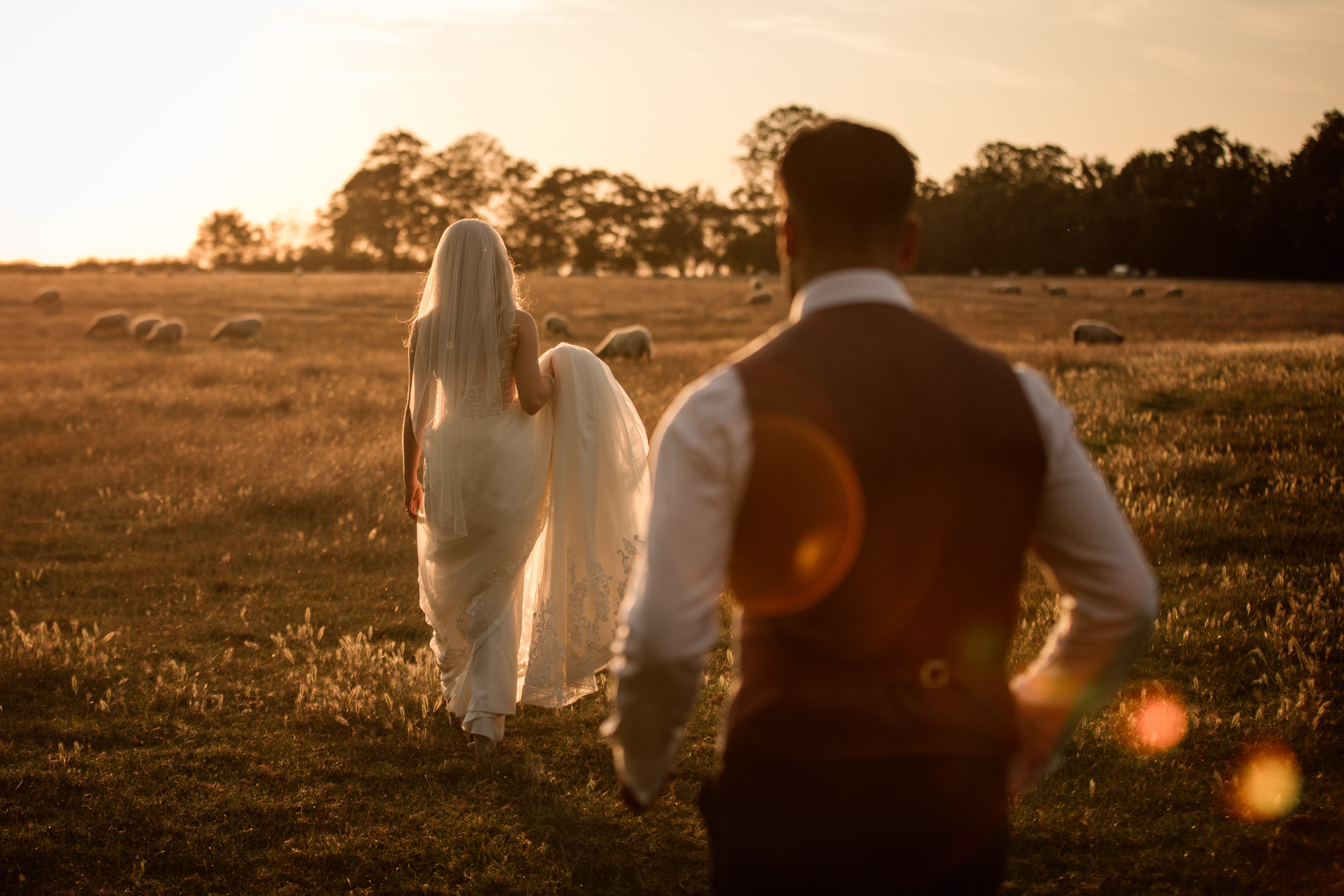 Bride and Groom walking through field at golden hour sunset