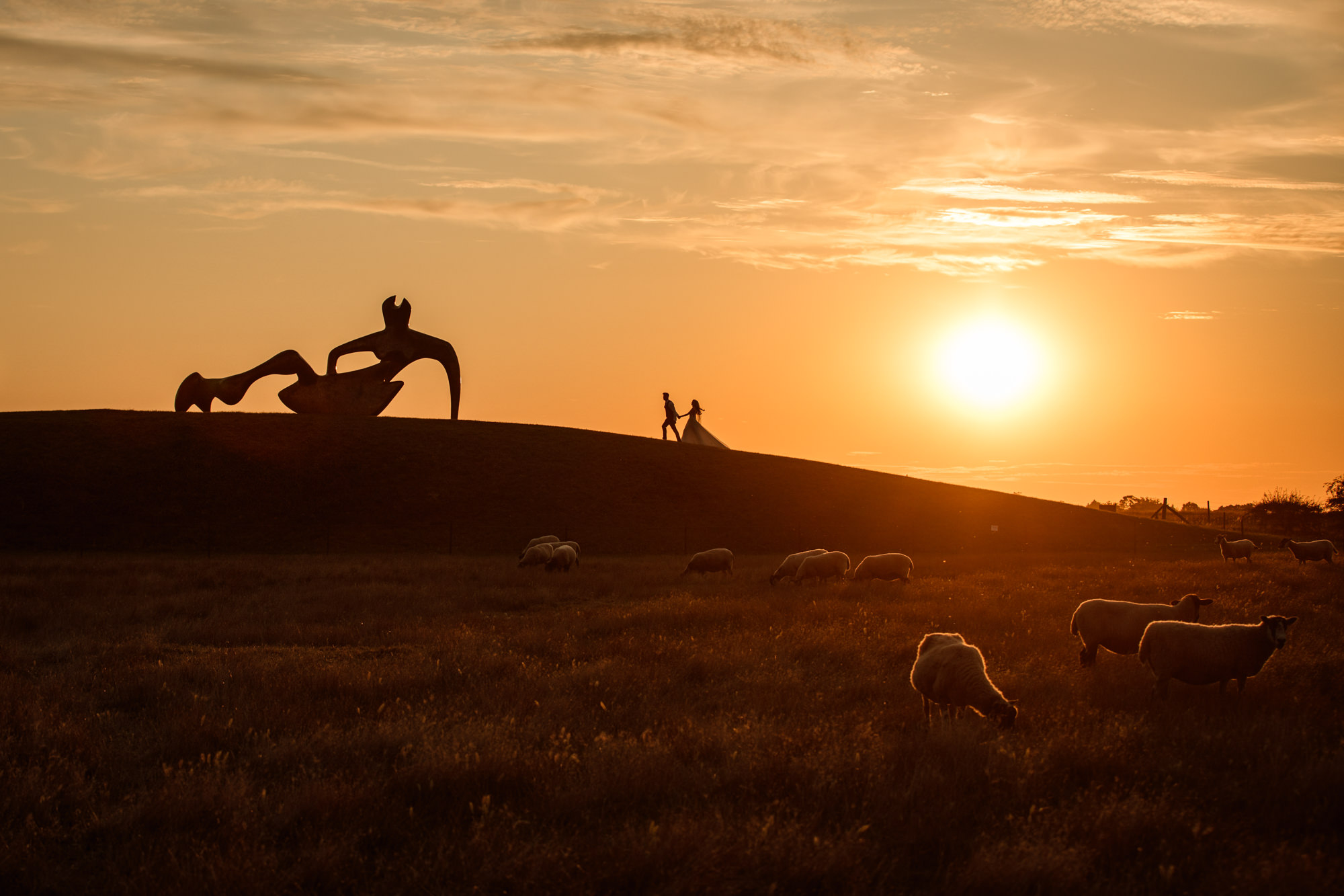 Bride and Groom walking up hill at sunset towards Henry Moore reclining figure