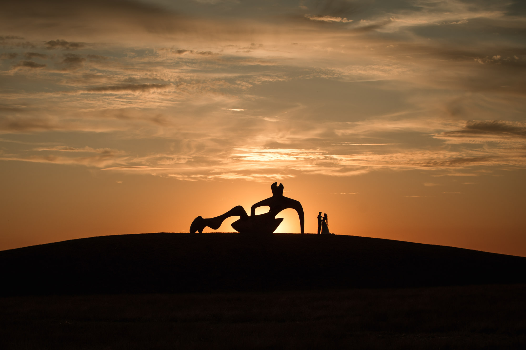 Bride and Groom and Henry Moore reclining figure back lit by sunset