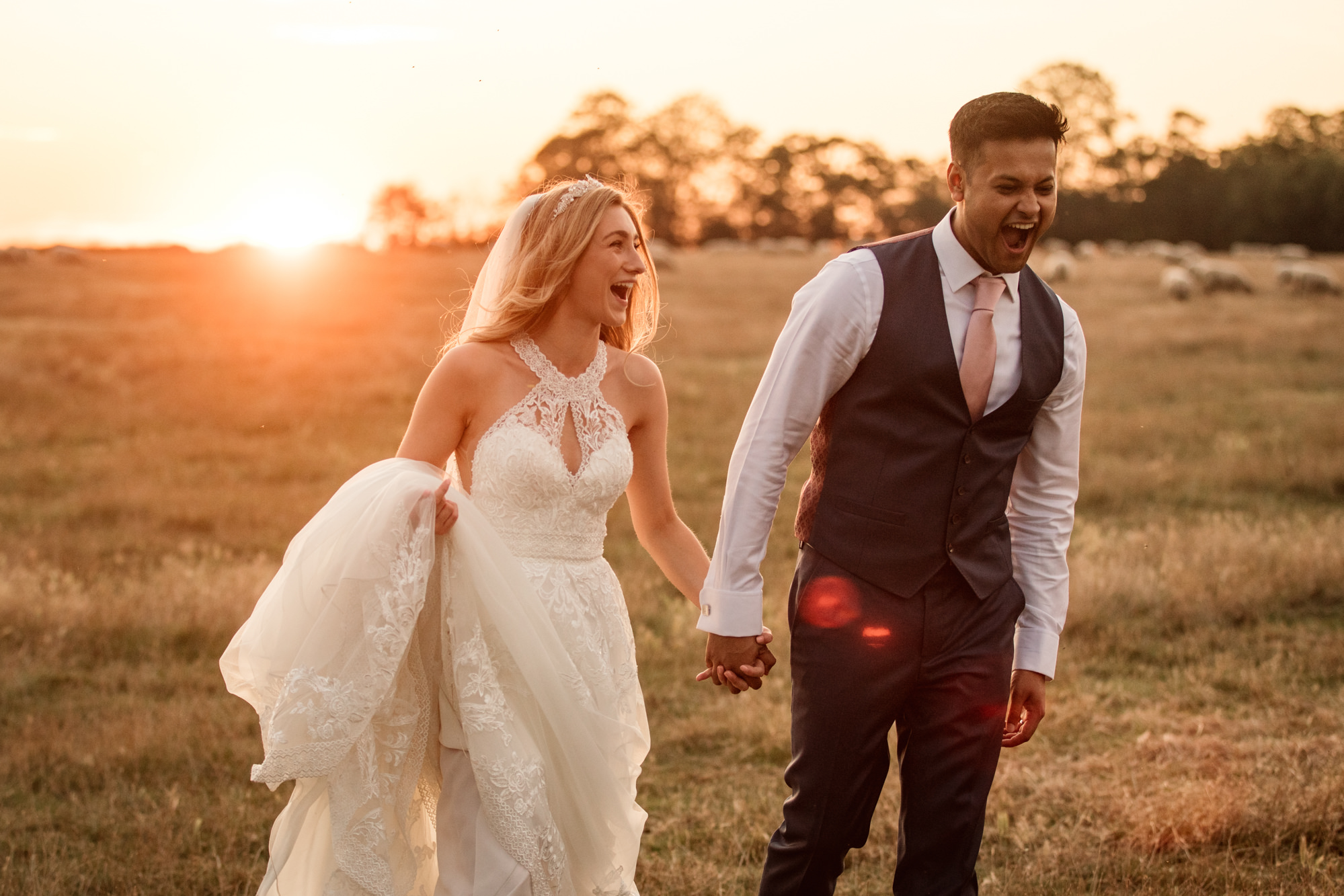 Bride and Groom walking and laughing at sunset