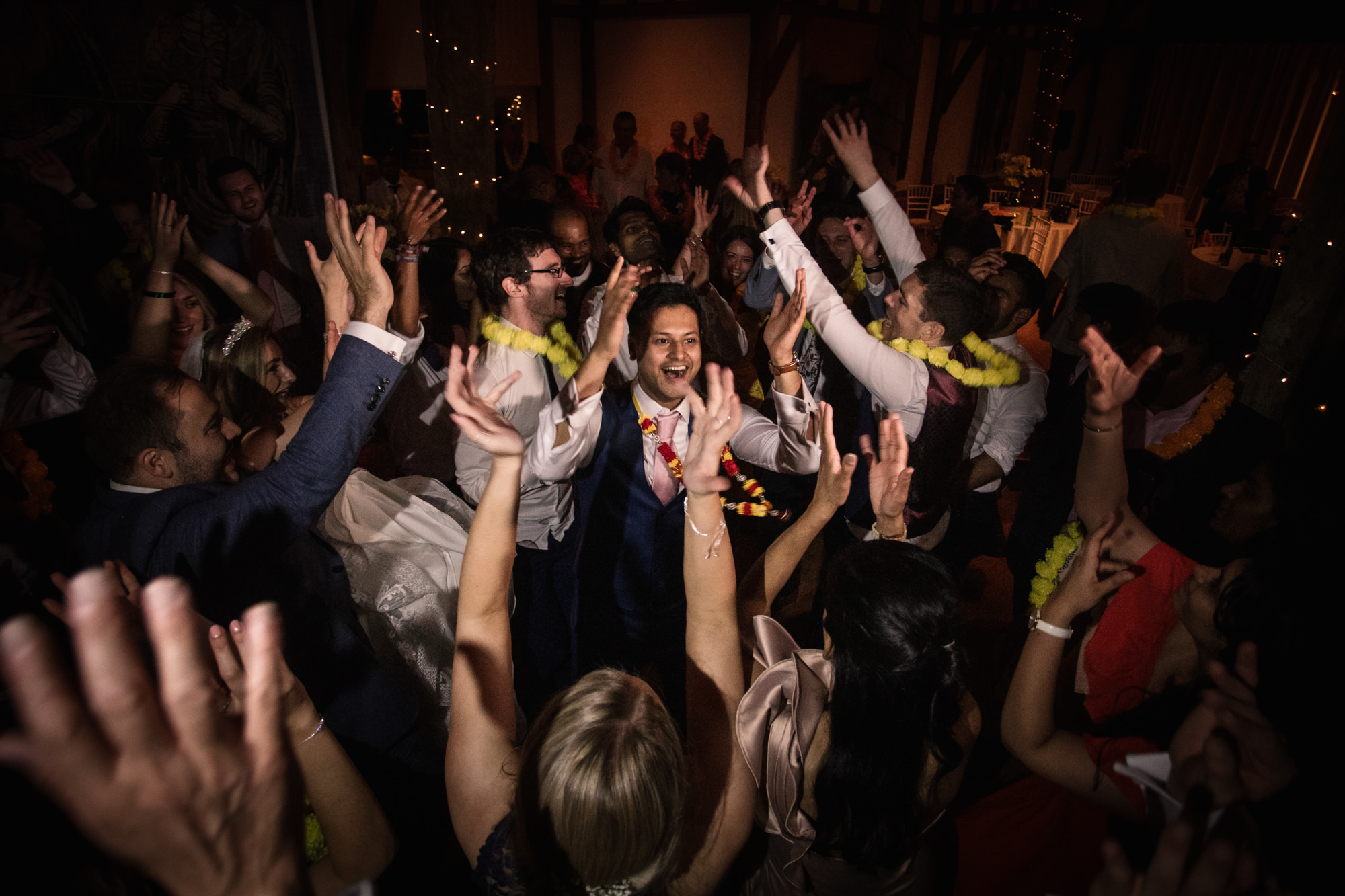 Groom dancing in the middle of guests at wedding reception party