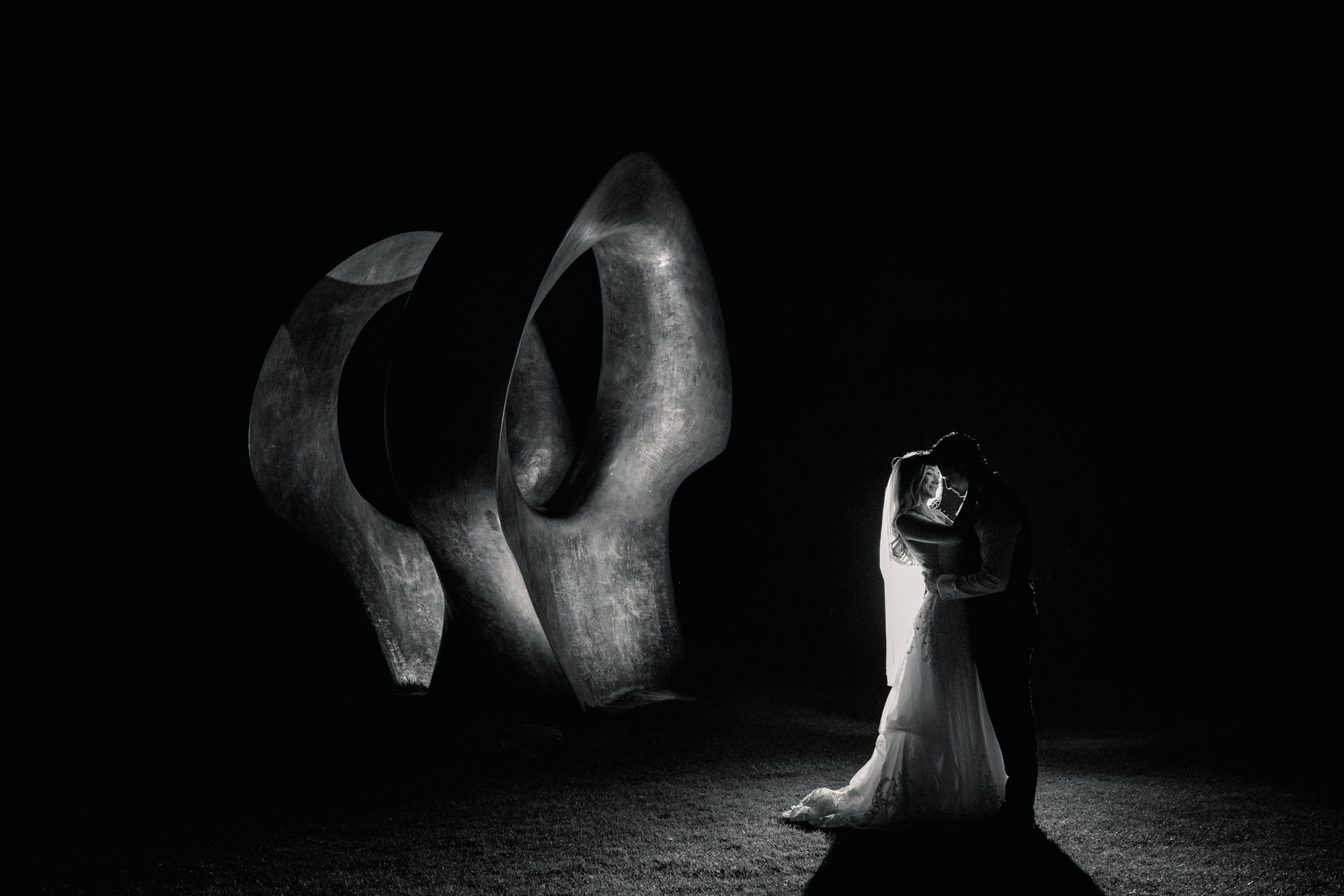 Silhouette of bride and groom with Henry Moore statue in black and white