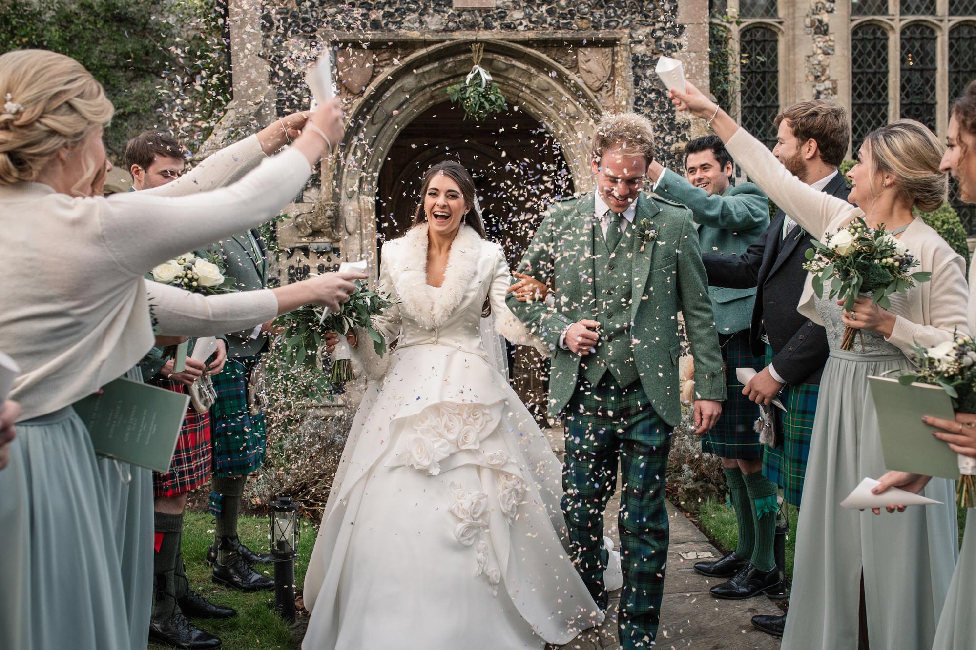Confetti throwing outside church of winter wedding